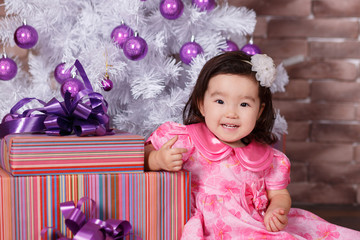 Asian pin up little cute girl wearing pink casual dress posing close to new year christmas white tree with violet purple balls toys and colourful presents