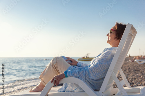 stylish attractive mature woman 50-60 years old sitting in a deckchair on the se Wallpaper Mural