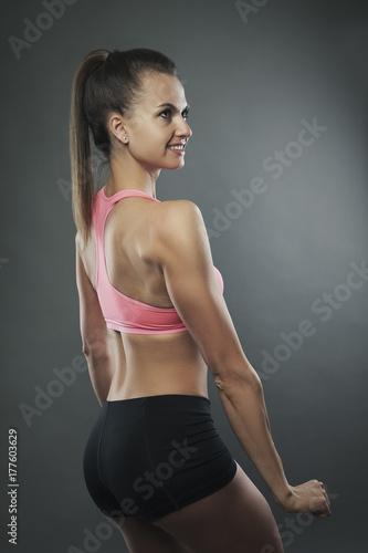 Plakat Sport kobieta z powrotem studio portret na ciemnym bg