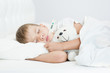 Sick boy with thermometer in mouth lying in bed and hugging a toy bear