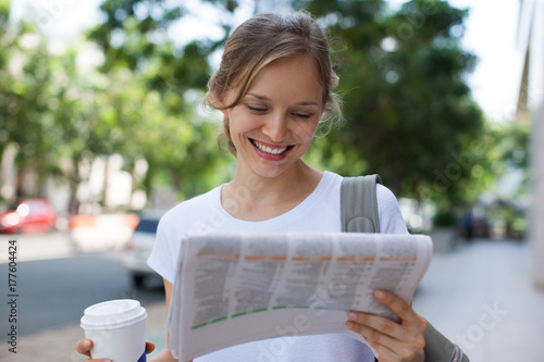 Leinwand Poster Smiling Woman Reading Newspaper on Street