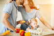 Happy couple kissing in kitchen while daughter sitting between them
