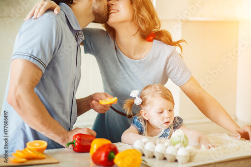 Plakat Szczęśliwy pary całowanie w kuchni podczas gdy córki obsiadanie między one