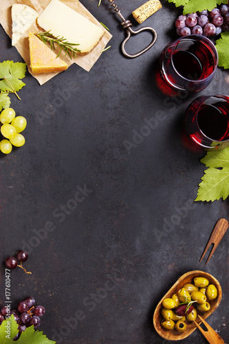 Wine appetizers set: French cheese selection, grapes and walnuts on rustic background