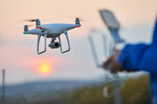 Obraz drone flying and operated by remote controlsunset - fototapety do salonu