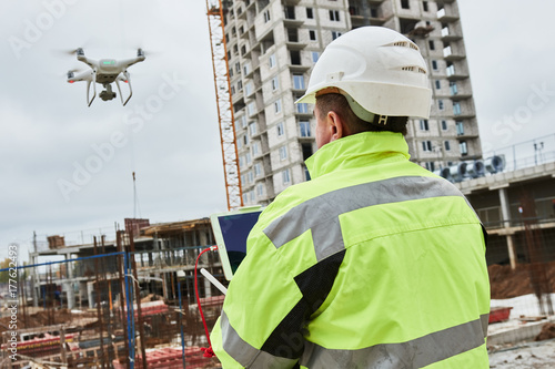 Fotografie, Obraz Drone operated by construction worker on building site
