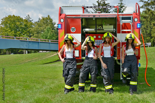 four female firefighters by a fire engine Canvas Print