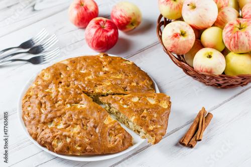 Plakat Domowej roboty jabłczany kulebiak z cynamonem i świeżymi dojrzałymi jabłkami w tle