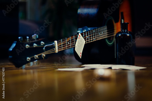 Cuadros en Lienzo  Liquor bottle, playing cards and guitar as a concept for alcoholism, addiction, rock'n'roll and ramshackle lifestyle