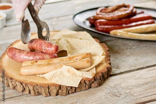 Plakat Szef kuchni wprowadzenie grillowane kiełbaski na naturalne drewno. Różne kiełbaski i lavash na drewnianym talerzu. Pyszne europejskie jedzenie.