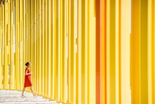 Woman In Red Dress Walking On The Modern Yellow Building Wall Background. General Plan With Abstract Geometric Composition