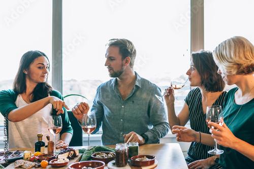 Plakat przyjaciele relaksują się i rozmawiają razem z winem i są gotowi do jedzenia