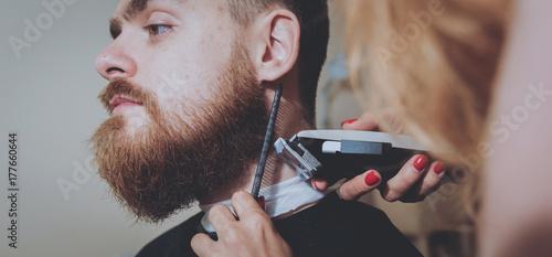 Plakat Mistrz tnie włosy i brodę mężczyzn, fryzjer tworzy fryzurę dla młodego mężczyzny. Hipsters