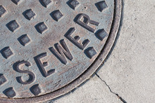 Metal Sewer Cover In Pavement....