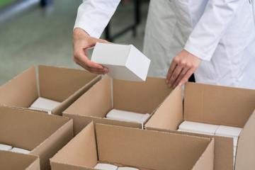 Detailansicht einer Arbeiterin, die Waren in Pakete verpackt und ausliefert