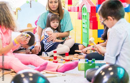 Valokuva  Gruppe von Kindern im Kindergarten mit Erzieherin beim Spielen