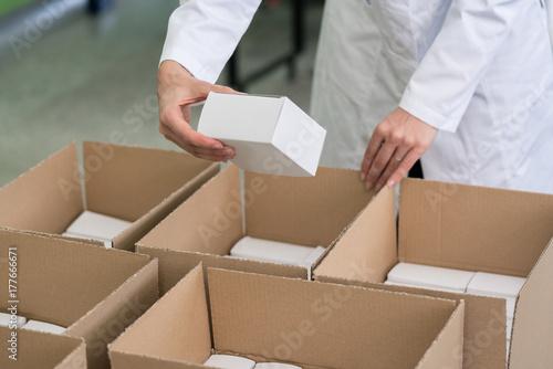 Fotografía  Detailansicht einer Arbeiterin, die Waren in Pakete verpackt und ausliefert