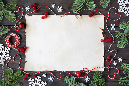 Fotografie, Obraz  Christmas wooden background with paper, snowflakes, branches tree, red berries a