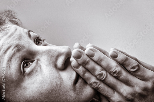 Dramatic, black and white image of a woman during a prayer on light background.