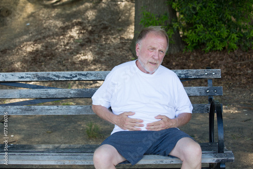Valokuva  Closeup portrait, old man clutching stomach, having belly pain, sitting on bench, isolated outdoors, green trees background