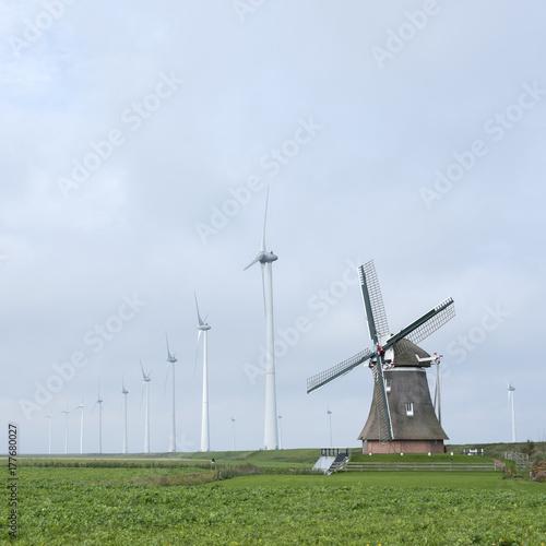 Zdjęcie XXL stary wiatrak goliath w roodeschool w holenderskiej prowincji groningen między rzędem nowoczesnych turbin wiatrowych