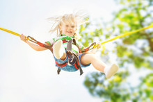 Happy Child Jumping With A Bungee At Summer Sky Background.