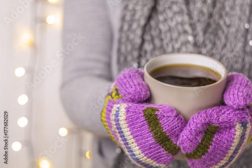 Plakat Kubek gorącej herbaty, napój w mitenkach. Bożenarodzeniowy pojęcie. Wystrój noworoczny. Girlandy i szalik.