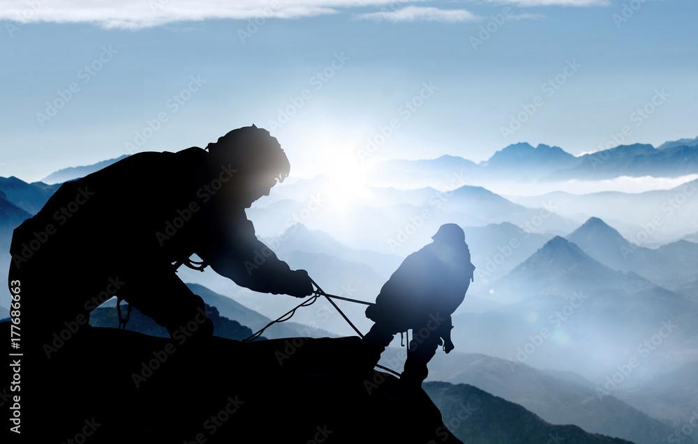 Fototapeta Hilfe beim Aufstieg - Bergsteiger auf einem Gipfel im Hochgebirge
