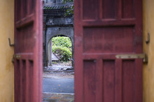 An Ancient Stone Arch Seen Through A Red Door Of A Buddhist Temple In Vietnam.