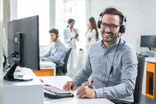 Happy Young Male Customer Support Executive Working In Office.
