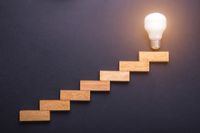 Wooden Block Set Up For Staircase With Light Bulbs On The Top Point On Black Stone Board. Business Success And Create Idea Concept