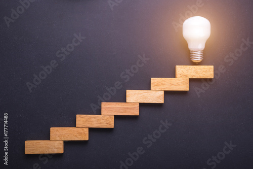Photo Wooden block set up for staircase with light bulbs on the top point on black stone board