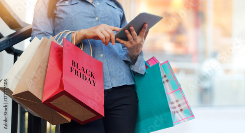 Fotografía  Woman using tablet and holding Black Friday shopping bag while standing on stair
