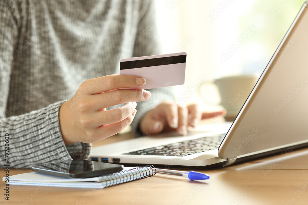 Fototapeta Woman hand paying on line with credit card