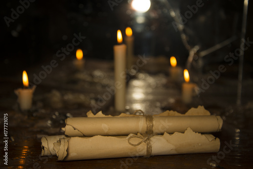 Fotografering  Mysterious ancient scrolls on the table with candles.