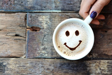 Happy Face On Cappuccino Foam, Woman Hands Holding One Cappuccino Cup On Wooden Table