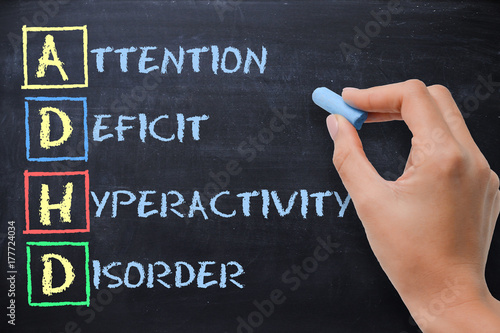 Photo ADHD – attention deficit hyperactivity disorder handwritten by woman on blackboa