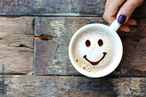 Leinwand Poster Happy face on cappuccino foam, woman hands holding one cappuccino cup on wooden