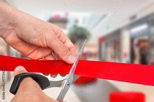 Photo Hand with scissors cutting red ribbon - opening ceremony