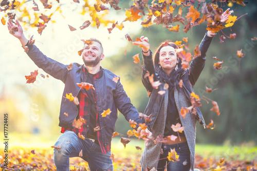 Plakat Młoda urocza szczęśliwa para - kochankowie lata z liśćmi w jesień parku