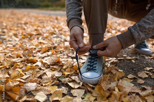 Zdjęcie XXL Mężczyzna wiążący sznurówki do butów przed bieganiem na świeżym powietrzu. Zdrowy tryb życia, człowiek jogginbg na zewnątrz.