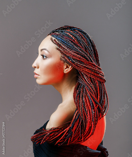 Fototapeta Women Hairstyle with colorful hair extensions braided in thin plaits and afrobra