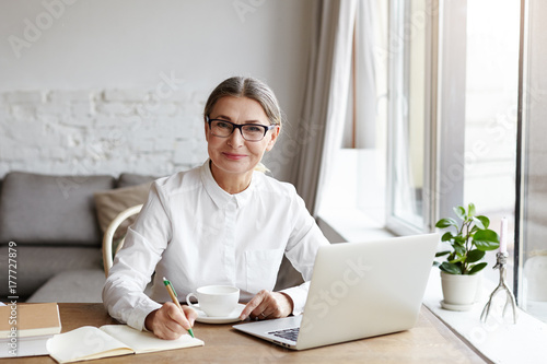 Fotografia  Attractive positive talented mature woman writer sitting in front of laptop and writing her new book about love, looking at camera with joyfull smile