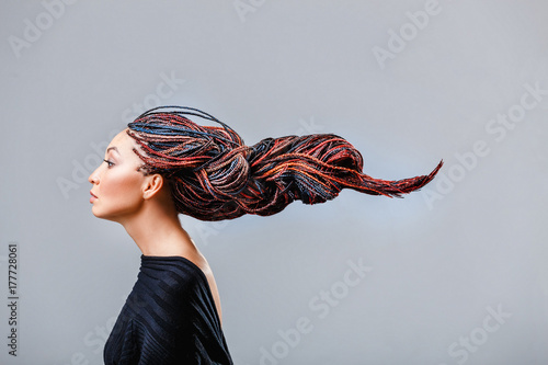 Fashion studio shoot of a mixed race woman with a creative colorful hairstyle in the form of a pigtail braided from dreadlocks in the technique of zizi Canvas Print