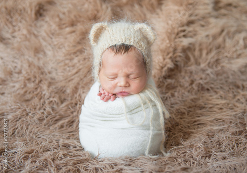 Fotografía  Child wrapped with white blanket, sleeping on furry surface
