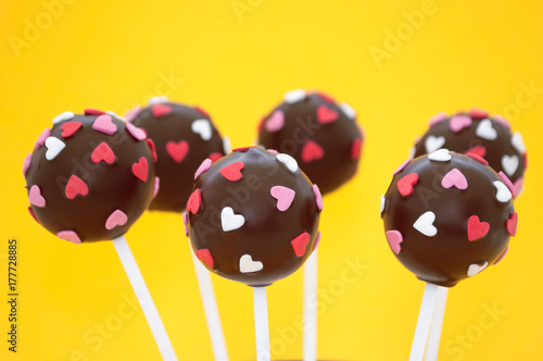 Photo  Chocolate cake pops, decorated with pink and white confectionery sprinkles in form of heart on a yellow background