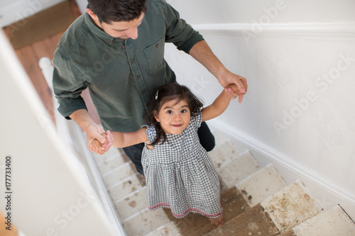 Father helping Daughter walk up stairs