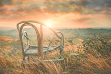 A Chair Is Situated On The Hill When The Sunset With The Silhouette Scene.