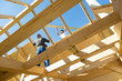 Roof builders mounting prefabricated wooden roof construction. Construction industry concept.