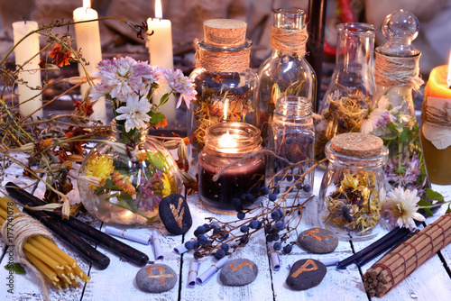 Fotografia Glass bottles, candles, runes and magic objects on witch table